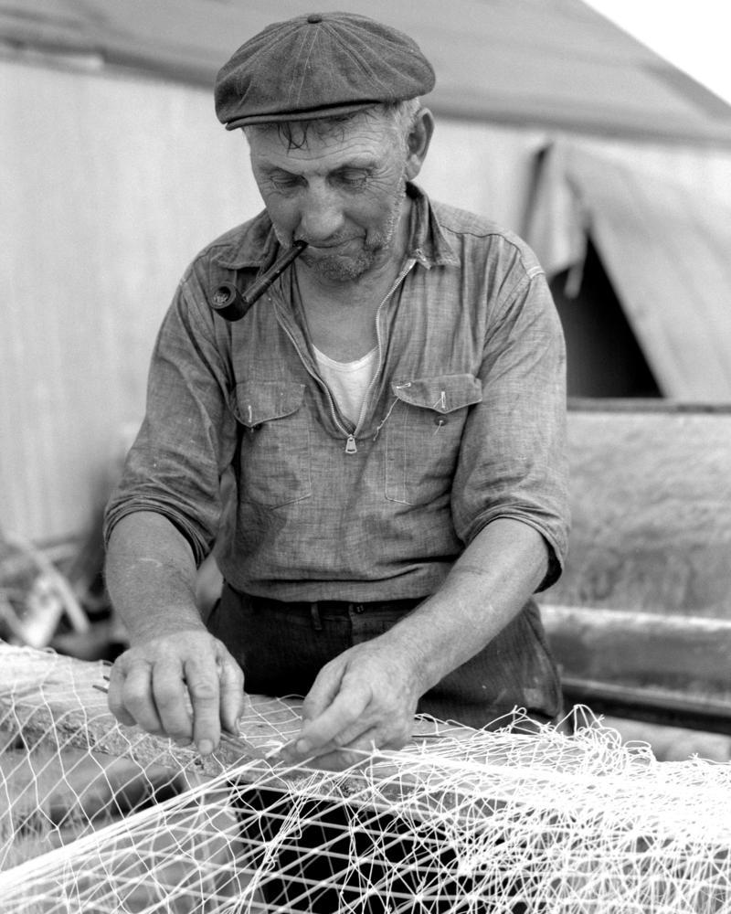 A fisherman repairs his net.
