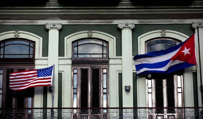The U.S. and Cuban flags fly outside a hotel in Havana.