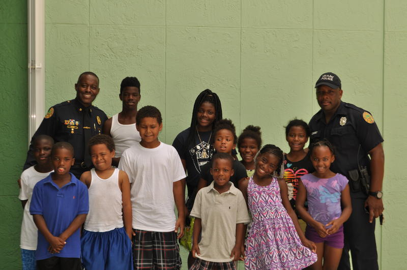 Liberty City neighborhood resource officer Daniel Mocombe  and Major Delrish Moss pose for a photo with the kids in Mocombe's summer reading club.