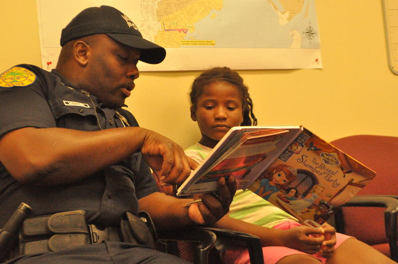 Liberty City neighborhood resource officer Daniel Mocombe reads to Raissa Coffie, 8, during his reading club.