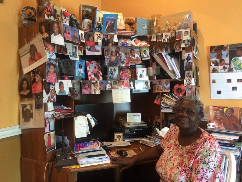Velmina Williams-Hamilton surrounded by pictures of her own family and kids she knows from the community