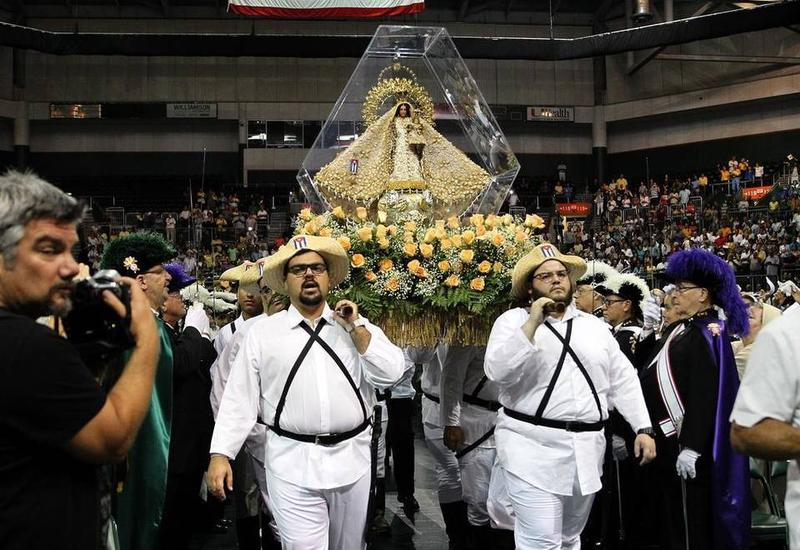Cuban-Americans in traditional garb carry Our Lady of Charity into Bank United Center in Coral Gables this month.