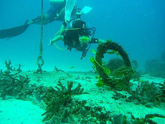 Jennifer Carraderro places a memorial wreath for her husband, Steve, at Neptune Society Memorial Reef.