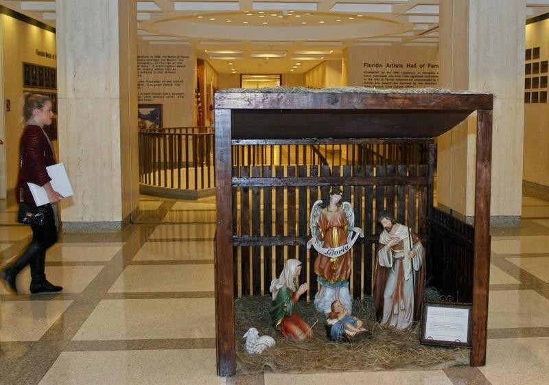 A woman walks past the Christmas nativity scene installed at the Florida Capitol in Tallahassee, Dec. 3, 2013.