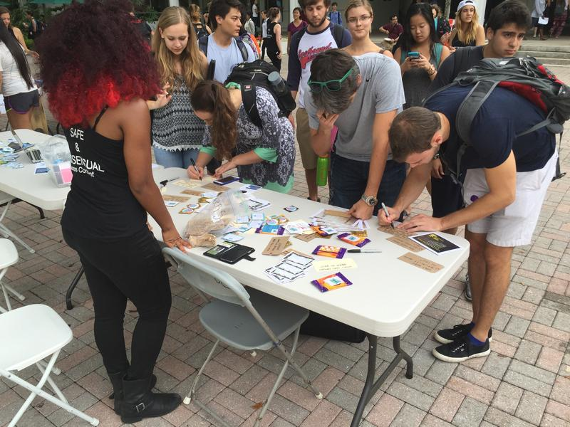 Student's write their answers to the problem of sexual assault at the Cane's Consent event.