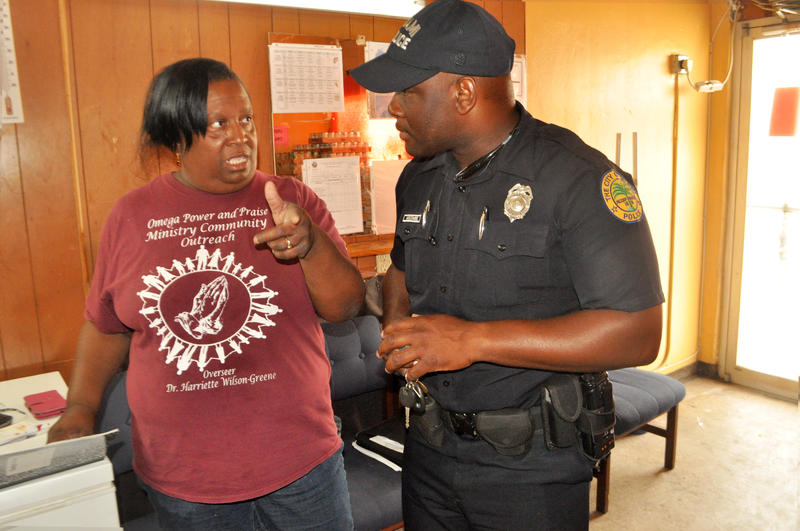 Officer Daniel Mocombe stops by Omega Power and Praise Ministry.  He meets with  Hariette Wilson Green,  who runs a food pantry at the church.