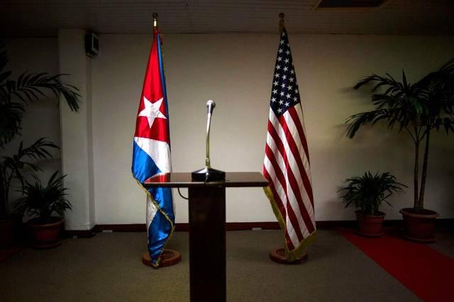 The United States and Cuba reestablished diplomatic relations early on July, 20, 2015. In this Jan. 22, 2015 file photo, a Cuban and U.S. flag stand before the start of a press conference on the sidelines of talks between the two nations in Havana.