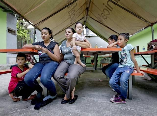 Marinelis Sabillón, 33, holds her 7-month-old daughter Kendy Julieth Briones Sabillón after she and her husband Menelio Briones and their five children arrived at El Edén center in San Pedro Sula, Honduras.