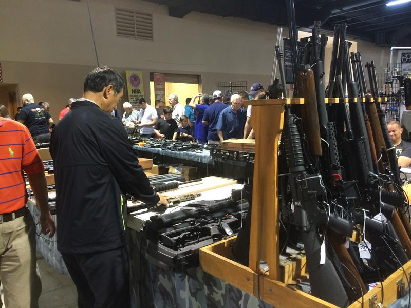 A prospective buyer examines guns at a gun show at the Miami-Dade fairgrounds on Saturday.