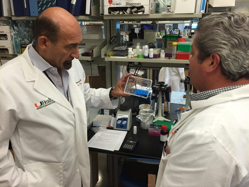 UM's Mario Stevenson (left) examines the new Zika virus detection test at his team's Miami lab.