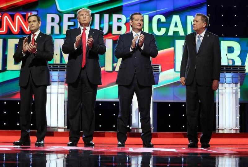 Republican presidential candidates Marco Rubio, Donald Trump, Ted Cruz and John Kasich stand up for the national anthem during the Republican presidential primary debate Thursday night at the University of Miami.