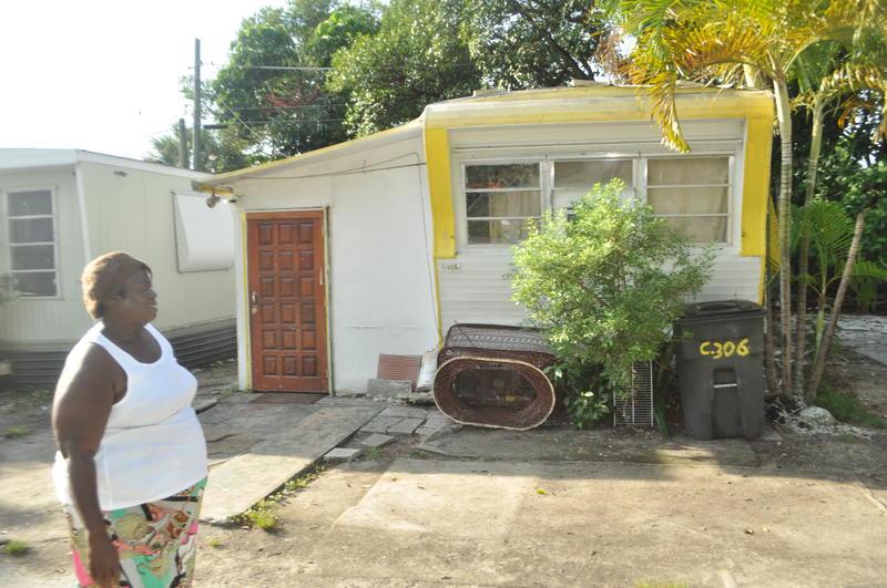 Little Farm trailer park resident Marie Janine Desir walks past a neighbor's trailer.