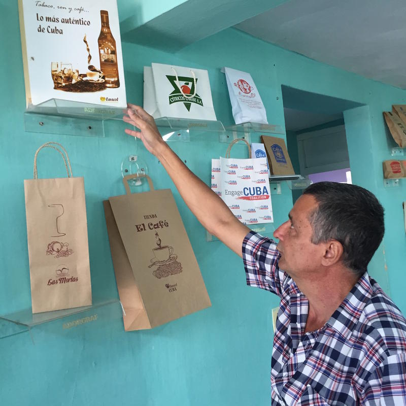 Rubén Valladares points to one of the printed bags he has made in his Havana workshop. His private company sells the bags to many Cuban state-owned companies.