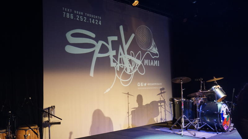 The stage at Speakfridays displays a projector screen with social media information and the show's logo. The cellphone number listed above is for audiences to text anonymous thoughts about the show.