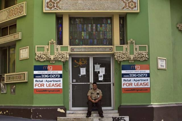 A security guard sits in front of a shuttered business in San Juan, Puerto Rico.