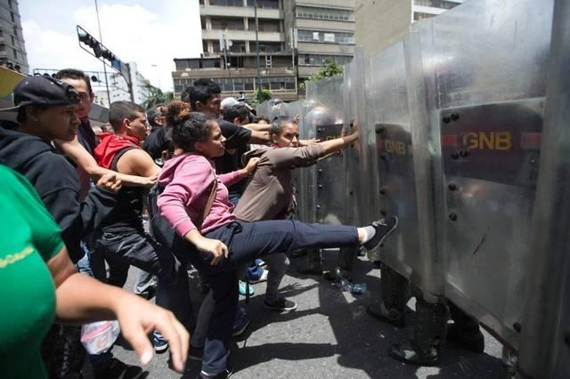 Venezuelans calling for the ouster of socialist President Nicolas Maduro confront riot police in Caracas.