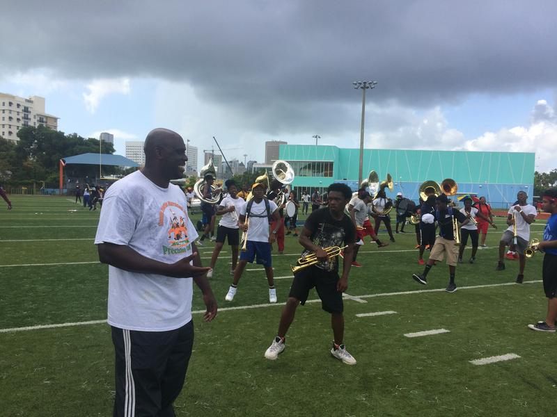South Broward High School Band Director Michael Scott walks through the horn section to keep the formation in check.