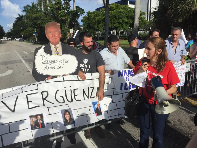 """Immigration advocates hold up their """"wall of shame"""" outside the Trump National Doral Miami resort to protest Donald Trump's immigration platform."""