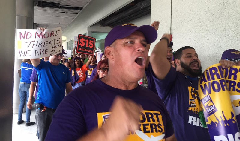 Triangle Services workers march at Terminal E at Miami International Airport
