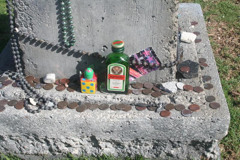 People don't just leave beads; they also leave offerings at the base of Captain Outrageous' monument.