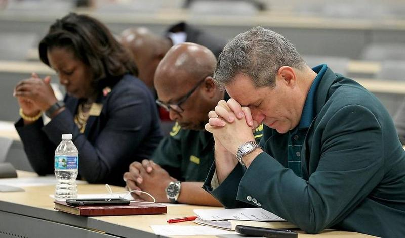 James DePelisi, director and chief executive officer the Broward Crime Commission puts his head down in prayer among fellow officers.
