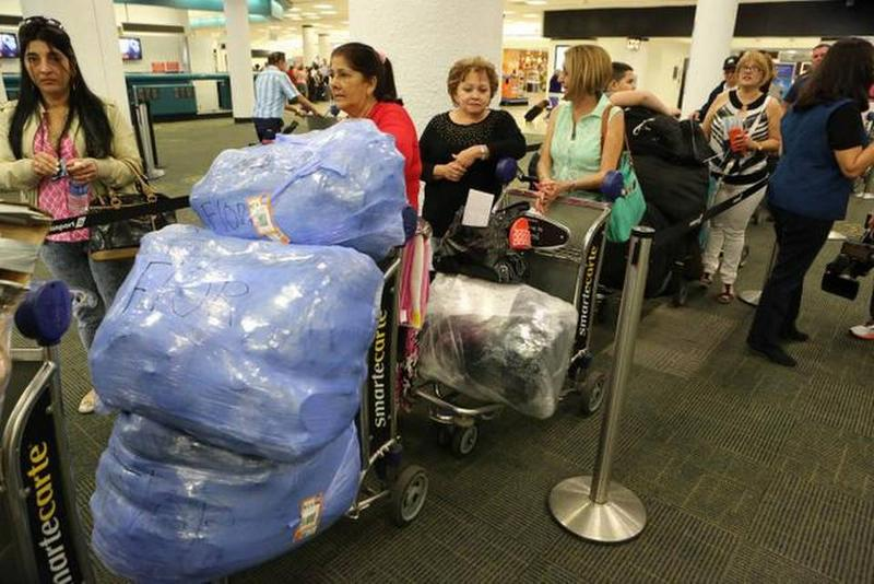 Cuban passengers check in at Miami International Airport with mounds of luggage for a charter flight to Havana.