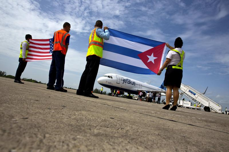 Airport workers receive JetBlue flight 387 holding a United States, and a Cuban national flag, on the airport tarmac in Santa Clara, Cuba, Wednesday, Aug. 31, 2016.