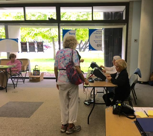 Two voters go through the verification process at the West Dade Regional Library before getting their ballot.