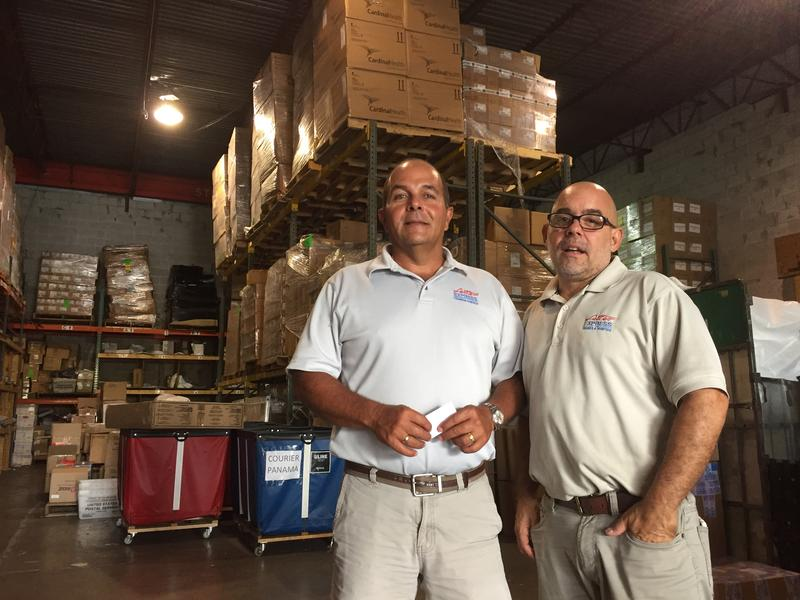 Rafael Landa (left) and Pedro Behrens, who run the Doral shipping firm Letter Express, in front of medical shipments bound for families in Venezuela.