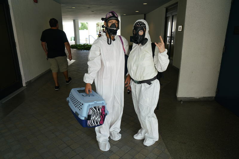 Aerial spraying opponents donned hazmat suits and respirators at a protest outside the Miami Beach City Center on Wednesday morning.