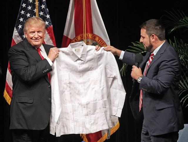 Donald Trump receives a traditional guayabera shirt from Miami state Rep. Carlos Trujillo at a Latino town hall meeting in Little Havana Tuesday