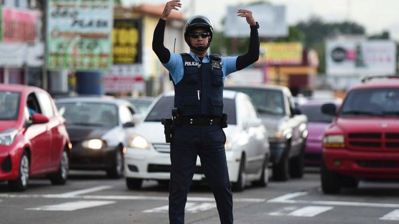 A police officer directs traffic in San Juan during Puerto Rico's island-wide blackout this week.