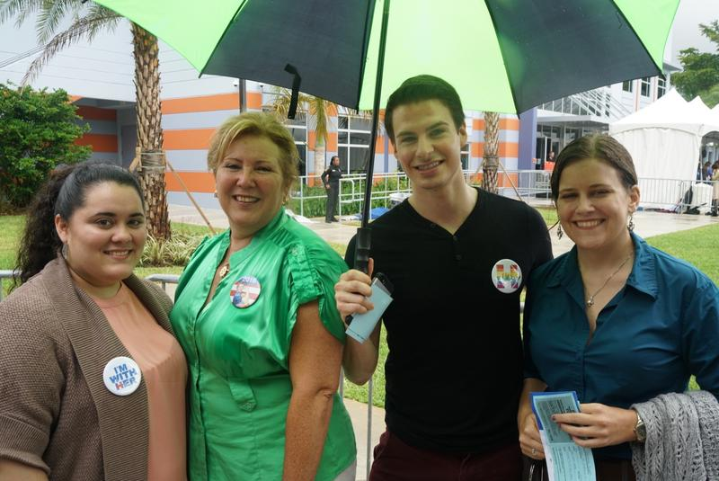 Thainy Diaz (left) huddled under a green and black umbrella with her mother and friends, while they waited to get into the FMU Arena.
