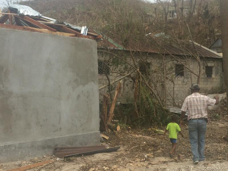A father and son walk past the damaged roof of the small corner store they own in Camp Perrin. Most of the merchandise was destroyed when water got into the store during the storm.