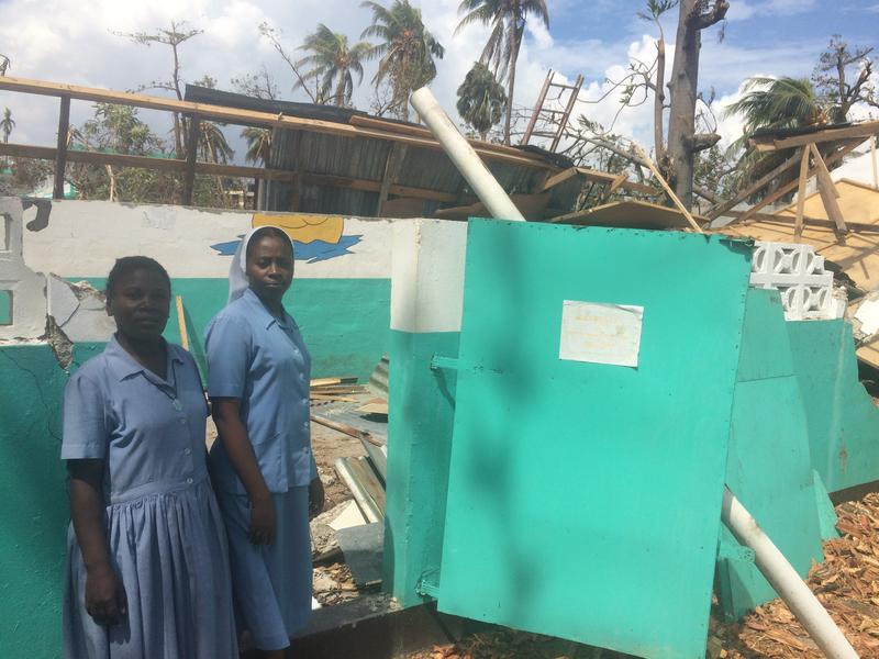 Sister Rose André, right, principal of École Normale Des Cayes, in front of two classrooms destroyed by the storm.
