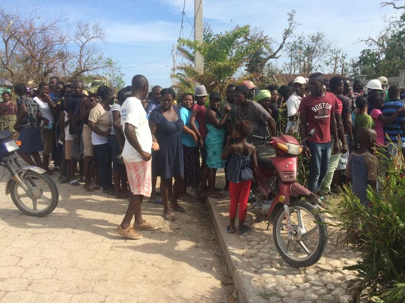 At a distribution in Torbeck, residents were suspicious of the process authorities used to decide who received aid. Here, a woman holds out her hand to ask a representative from the Civil Protection Department for a ticket.