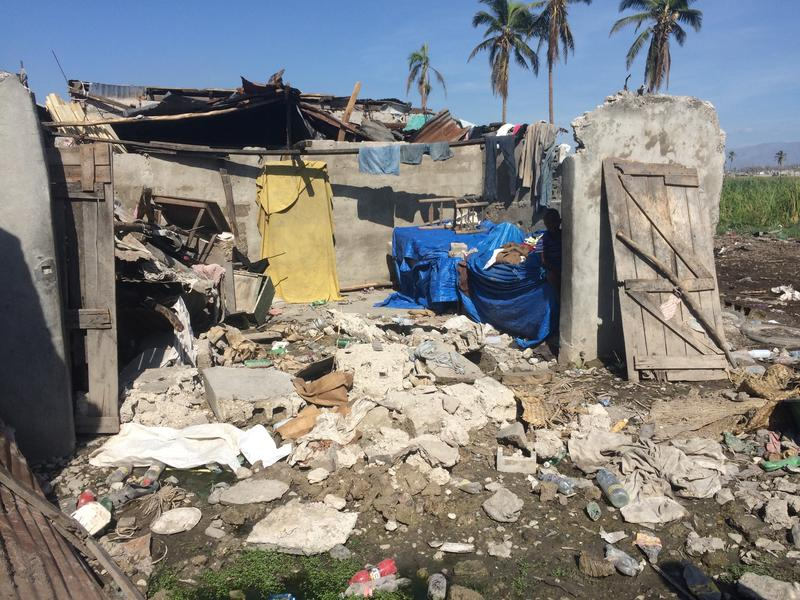 A boy peaks his head out from the shade of what's left of a house in Lasinal, a neighborhood in Les Cayes.