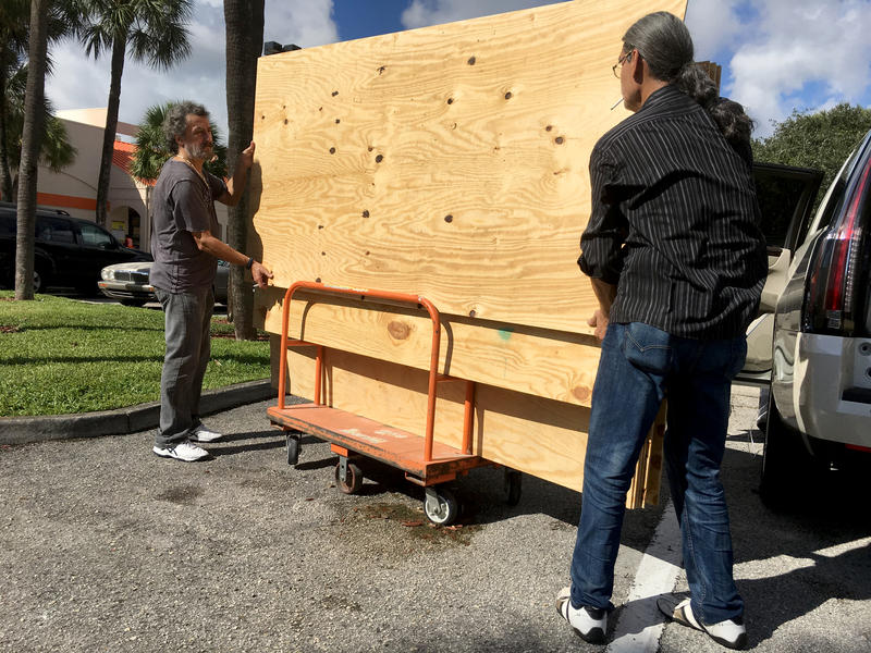 Brothers Danny Delarocca, left and Gino Delarocca, right, both of Boca Raton, load plywood onto their car at the Home Depot in Deerfield Beach, Fla. Tuesday, Oct. 4, 2016.