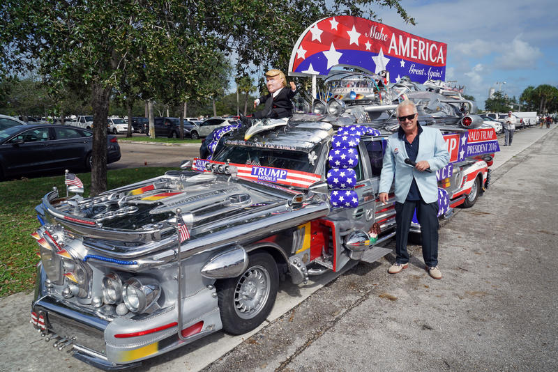 Ronn Royce stands in front of the Trump Mobile, which sat on display in the parking lot outside the South Florida Fair Expo Center, before the Donald Trump rally in West Palm Beach on October 13, 2106.