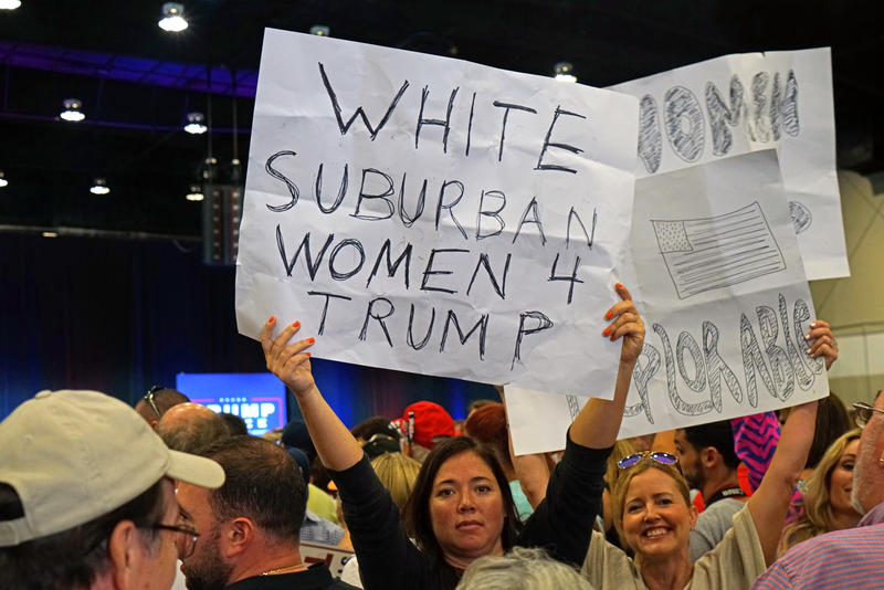 "A Trump supporter stands in the crowd holding a ""White Suburban Women 4 Trump"" sign at a rally in West Palm Beach on October 13, 2016."