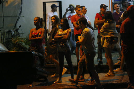 People stand in the street after nightclubs were closed by authorities following the announcement of Fidel Castro's death in Havana, Cuba, early Saturday, Nov. 26, 2016.