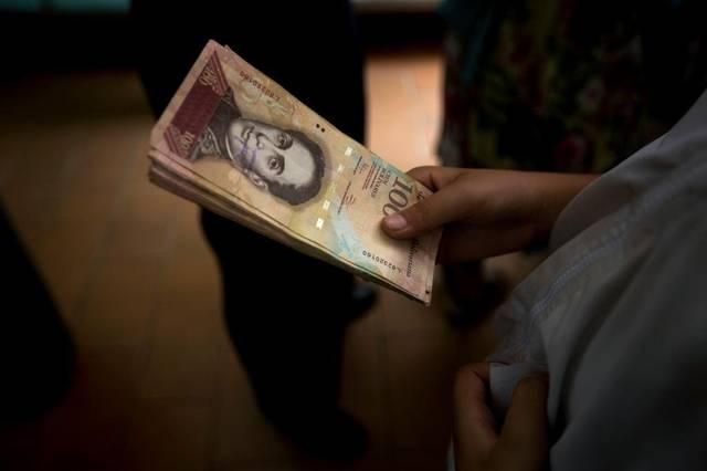 A Venezuelan holds a stack of 100-bolivar bills that have become almost worthless amid the country's hyperinflation.