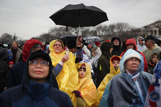 Spectators wait in the rain on the National Mall in Washington, Friday, Jan. 20, 2017, before the presidential inauguration of Donald Trump.