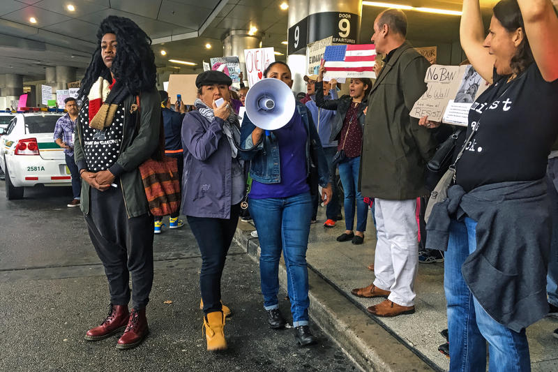 "Octavia Yearwood, 33, stood on the pavement between police and hundreds of protesters at Miami International Airport on Jan. 29, 2017. ""Police told us to get off the street, but I don't want to get off the street,"" she said."