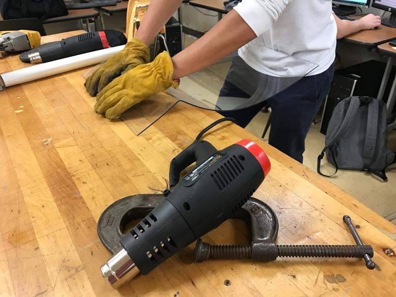 A RamTech59 student is building bending plastic to fit onto a robot that will be shooting wiffle balls into a nine-foot high target.