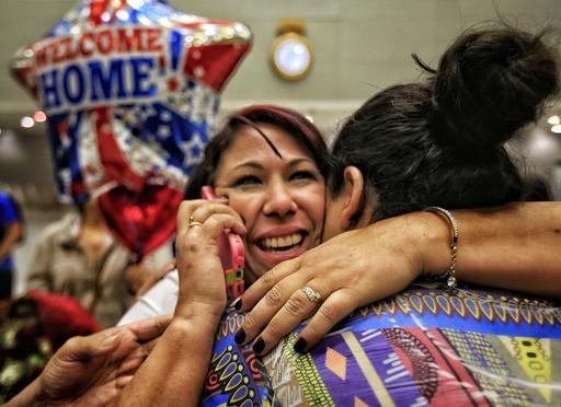Cuban health worker Veidy Diaz, center, is greeted by family and friends as she talks on the phone after finally leaving the immigration and customs section of Miami International Airport on Feb. 6, 2017.