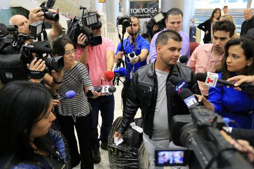 Cuban doctor Carlos Amigo, right, is surrounded by the media after arriving from Colombia at Miami International Airport on Feb. 6, 2017.