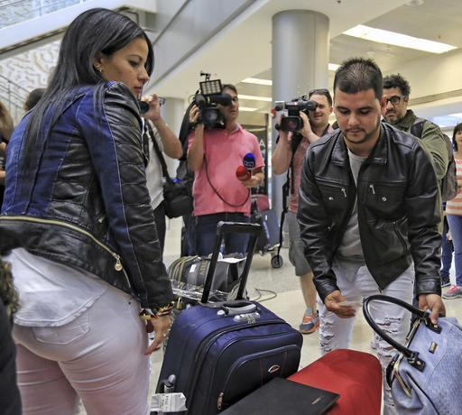 Cuban doctors Yerenia Cedeño, left, and Carlos Amigo, right, gather their belongings after arriving at Miami International Airport from Colombia on Feb. 6, 2017.