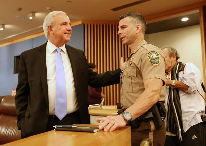 Miami-Dade Mayor Carlos Gimenez chats with Police Director Juan Pérez during Friday's commission meeting.