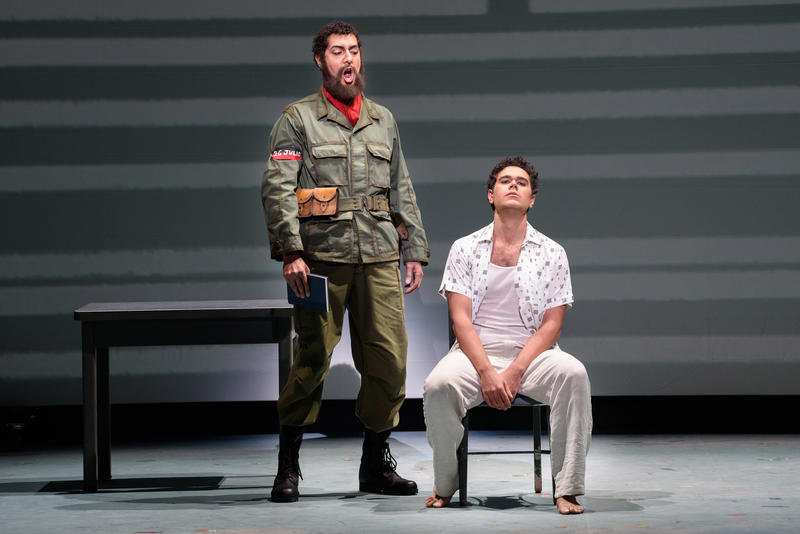 "Calvin Griffin (L) as Revolutionary official Victor and Elliot Madore (R), as Cuban writer Reinaldo Arenas in Florida Grand Opera's production of ""Before Night Falls."""